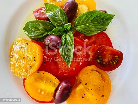 High angle closeup view of sliced red and yellow tomatoes, yellow cherry tomatoes and Black Russian cherry tomatoes with organic Australian black kalamata olives, sprigs of fresh home grown organic Basil, organic Spanish olive oil, sea salt and ground black pepper on a round white French ceramic plate on a wooden table