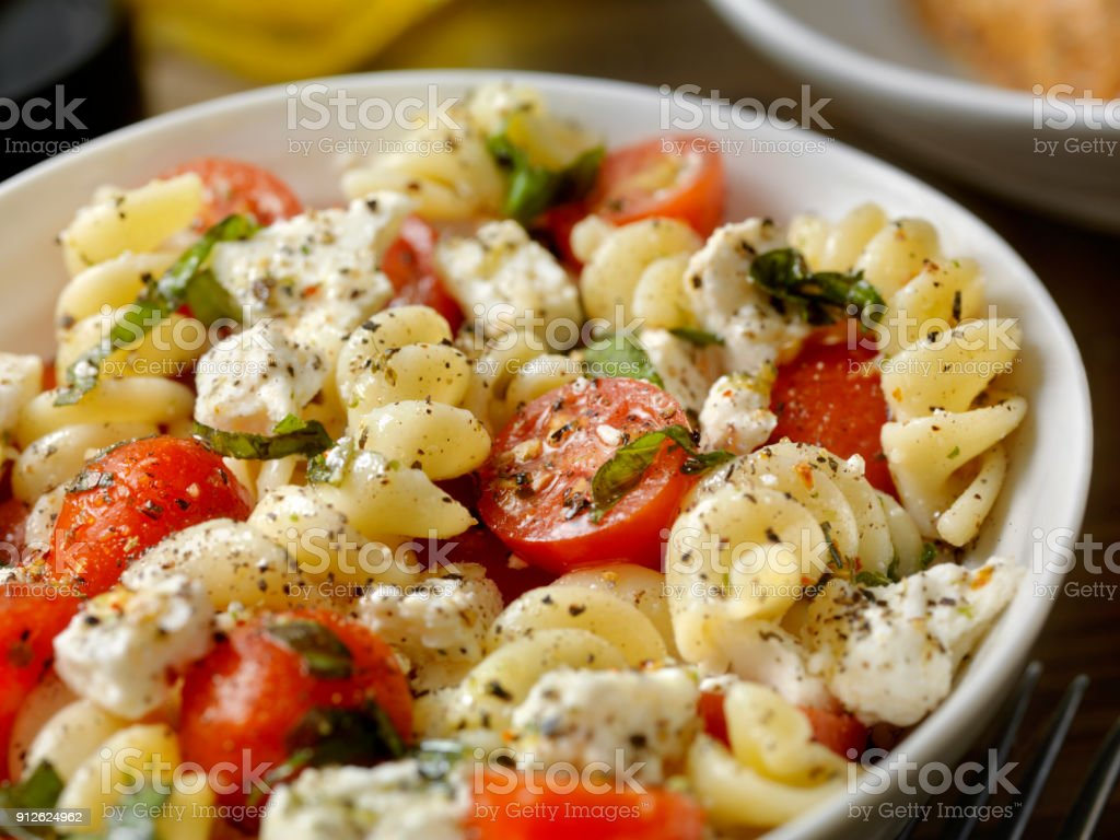 Pasta-Salat mit frisch gehacktem Basilikum, Tomaten und Feta – Foto