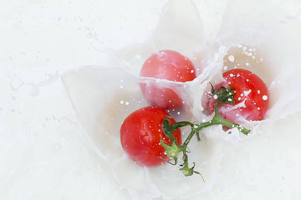 Tomate y salpicaduras de leche - foto de stock