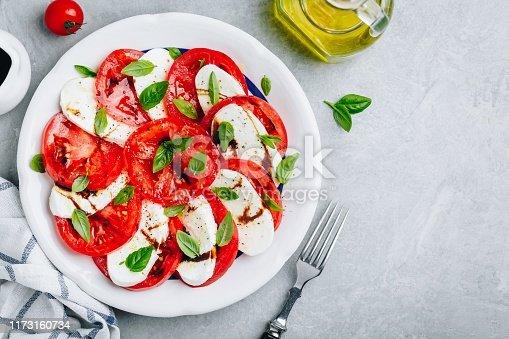 Tomato, basil, mozzarella Caprese salad with balsamic vinegar and olive oil. Top view, gray stone background