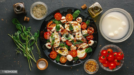 Ingredients for italian caprese salad. Mozzarella balls, tomatoes, basil leaves, olive oil with balsamic vinegar over concrete background