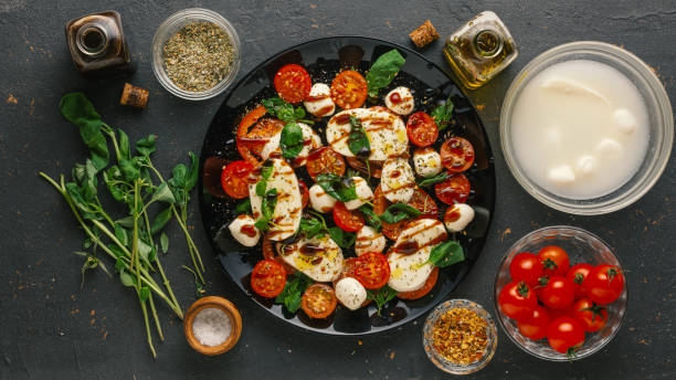 tomato basil, pesto sauce, basil pesto, pasta salad, burrata, insalata caprese, tomato mozzarella cheese stock photo