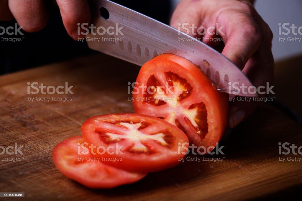 蕃茄被鋒利的刀子切開了 - 免版稅一片圖庫照片