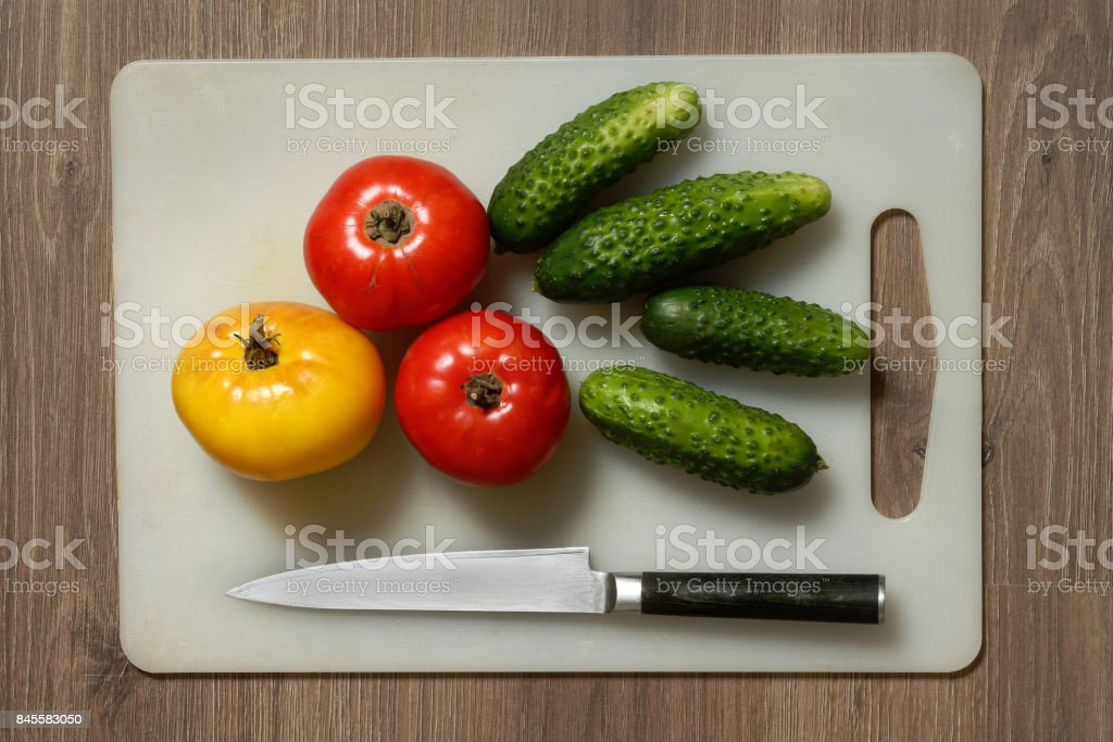 Tomato, cucumber and knife on cutting board. stock photo