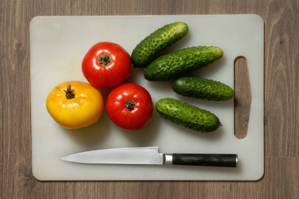 Cтоковое фото Tomato, cucumber and knife on cutting board.