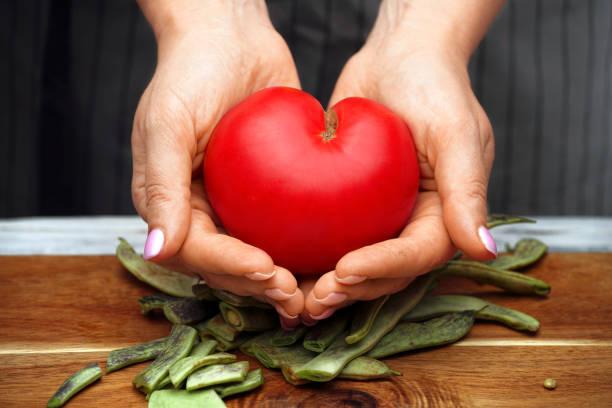 Tomate en forma de corazón en manos femeninas. Comida saludable. - foto de stock