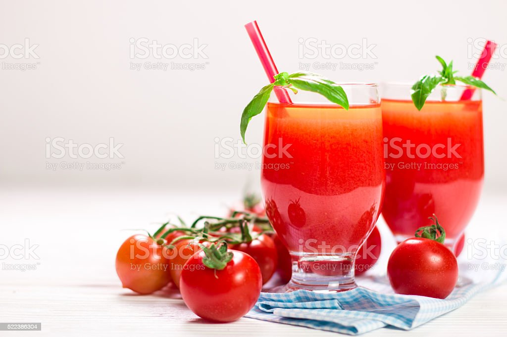 Tomato Juice and Fresh Tomatoes on a White Wooden Background stock photo