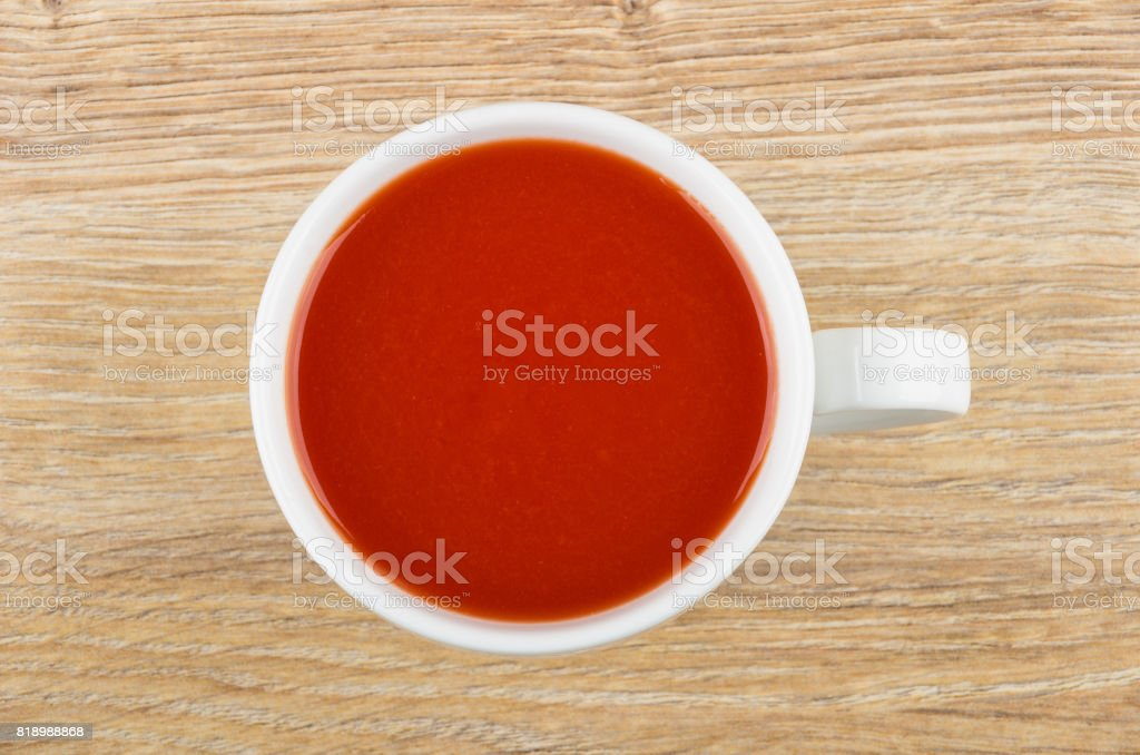 Tomato juice in white cup on wooden table stock photo