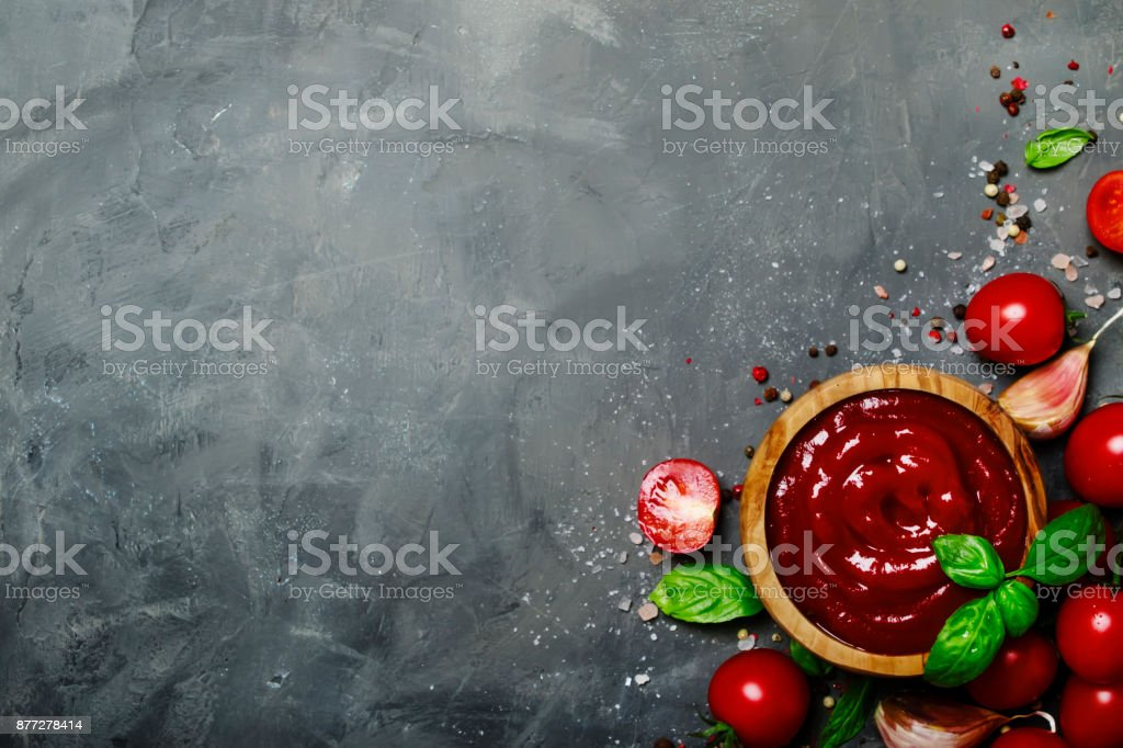 Tomato ketchup sauce with garlic, spices and herbs with cherry tomatoes stock photo