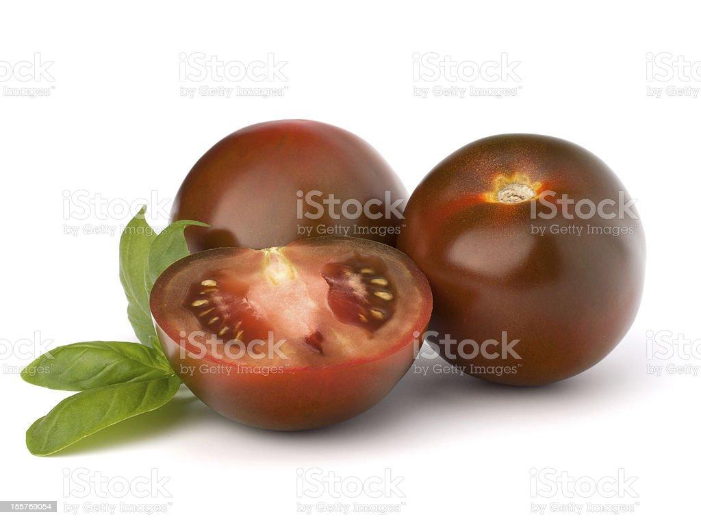 Tomato kumato and basil leaf stock photo