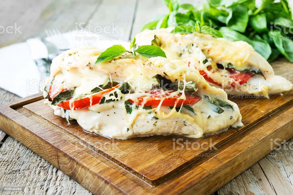 Tomato, mozzarella and basil stuffed chicken breasts stock photo