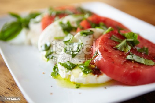 Tomato salad with basil, olive oil and black pepper shot with shallow focus on front.