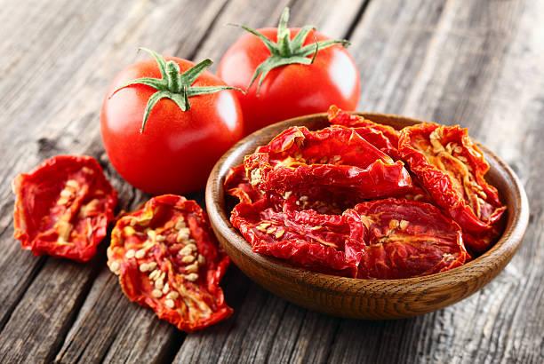 pomidory na drewnianym tle - suszony produkt zdjęcia i obrazy z banku zdjęć