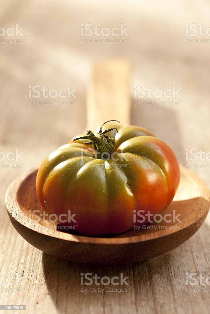 Tomato on a wooden spoon royalty-free stock photo