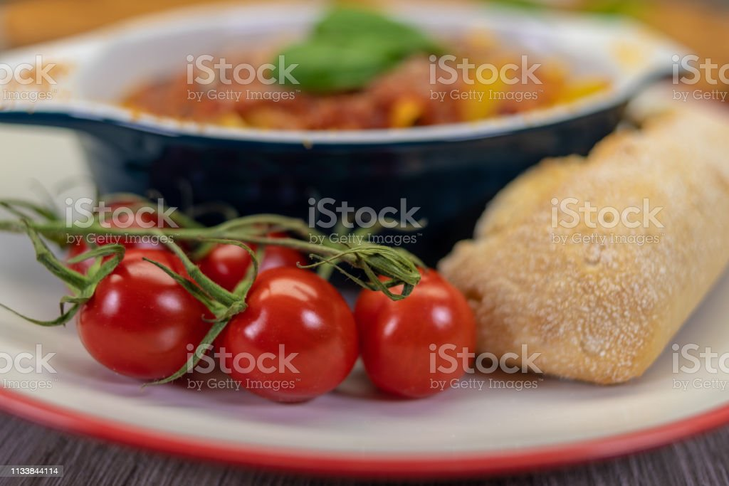 Tomato pasta bake meal with bread stock photo