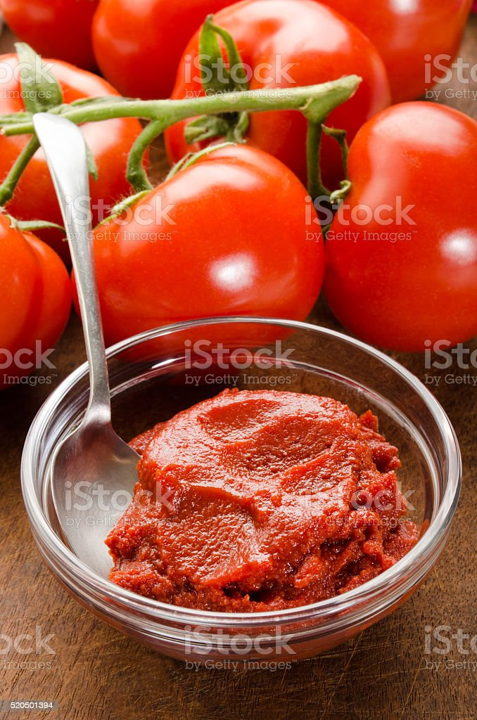 tomato paste in a glass bowl and spoon stock photo