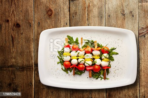 Directly above shot of Tomato, pepper and mozzarella skewers on a bed of dressed Rocket served in a plate