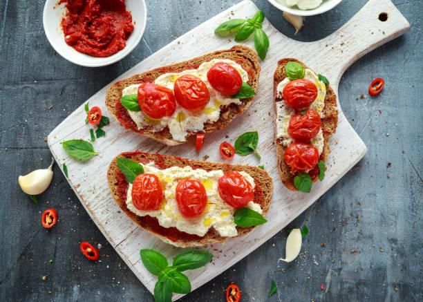 tomate-ricotta-bruschetta mit sonne getrockneten tomaten paste, schwarzbrot olivenöl und basilikum in eine hölzerne tafel. - ricotta stock-fotos und bilder