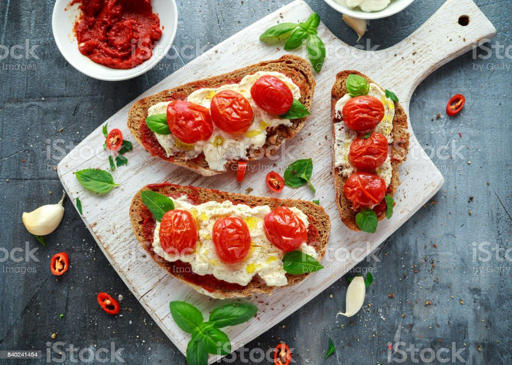 Tomato Ricotta Bruschetta with sun dried tomatoes paste, olive oil brown bread and basil in a white wooden board. стоковое фото