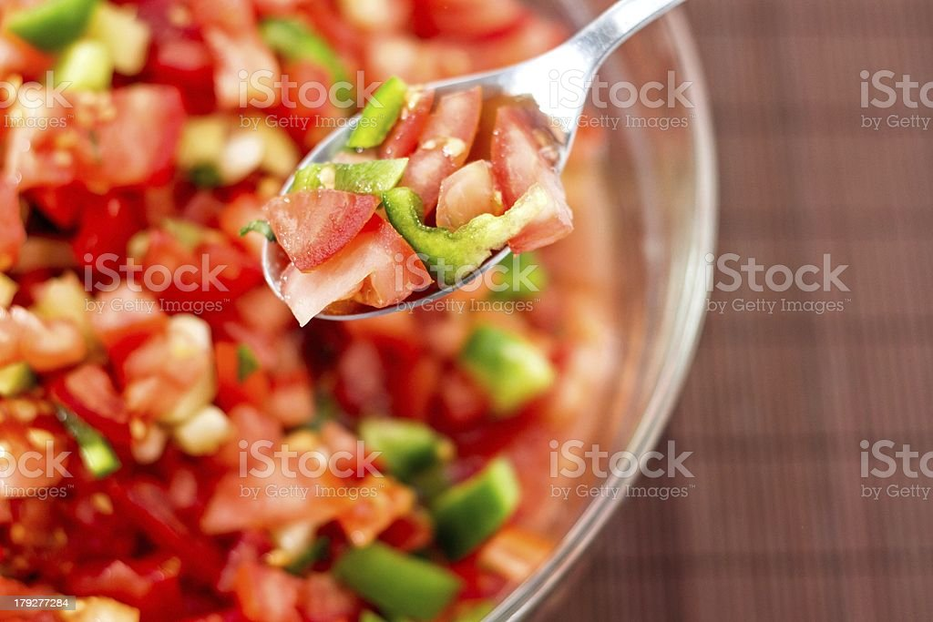 Tomato salad with green and yellow pepper on a spoon stock photo