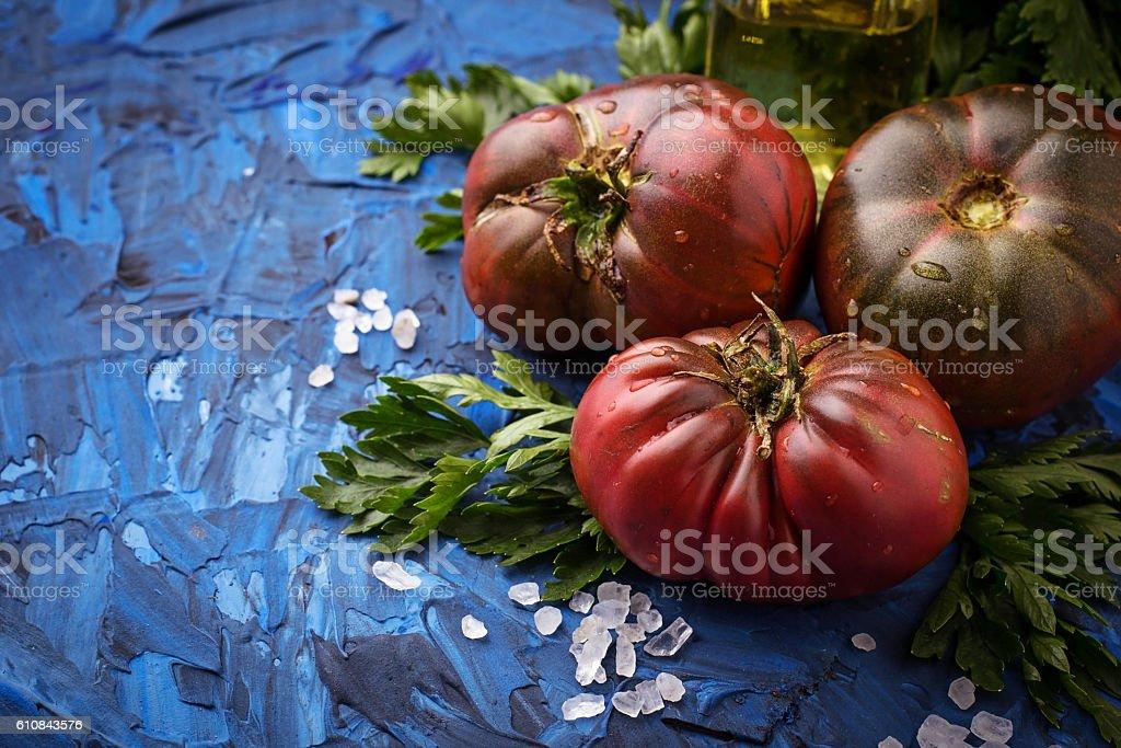 Tomato, salt and parsley on blue concrete background stock photo