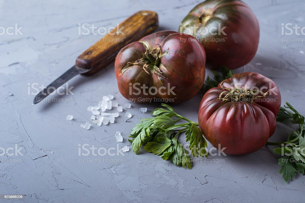 Tomato, salt, parsley and knife on gray concrete background stock photo