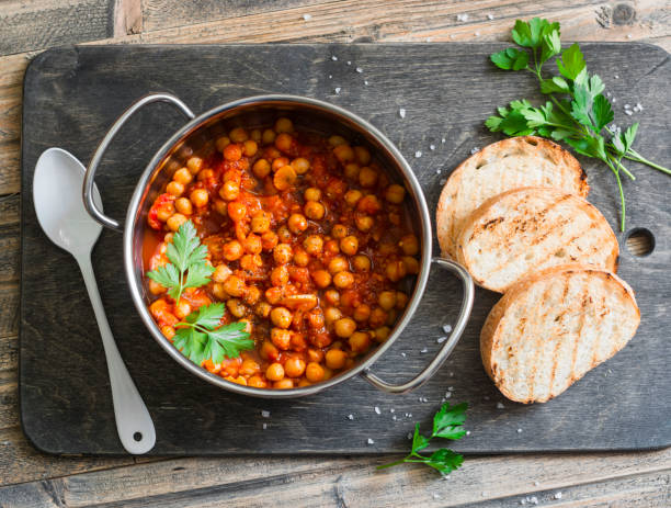 Tomato sauce braised chickpeas in a pot, and grilled bread. Delicious vegetarian lunch on a rustic wooden background, top view Tomato sauce braised chickpeas in a pot, and grilled bread. Delicious vegetarian lunch on a rustic wooden background, top view stew stock pictures, royalty-free photos & images