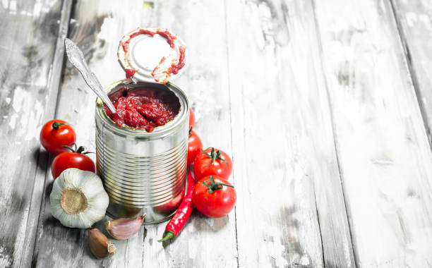 tomato sauce in a tin can with a spoon and tomatoes. - tomato can stock photos and pictures