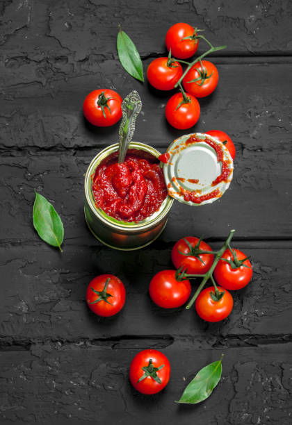 tomato sauce in a tin can with a spoon, leaves and tomatoes. - tomato can stock photos and pictures
