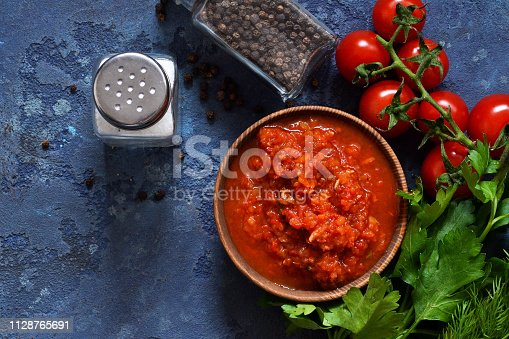 istock Tomato sauce with peppers, spices and herbs on the kitchen table. View from above. 1128765691