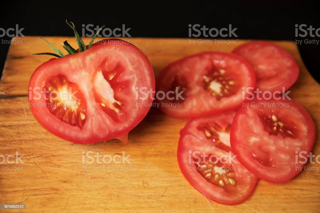 Tomato sliced on wooden cooking table stock photo