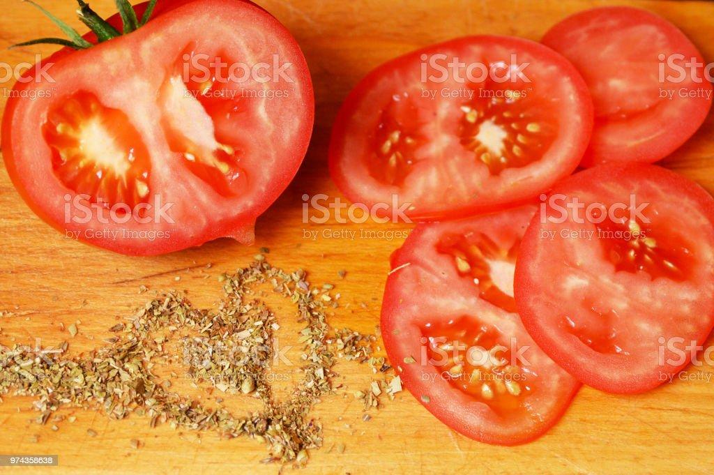 Tomato sliced, oregano shaped stock photo