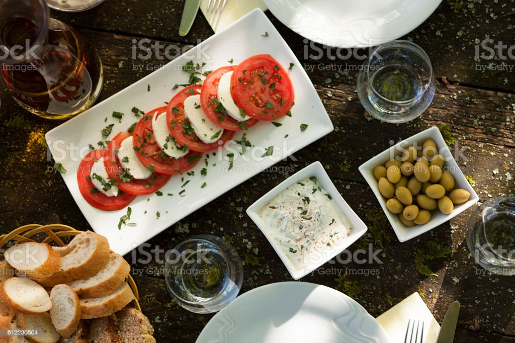 Tomato slices salad with cheese on a picnic table stock photo
