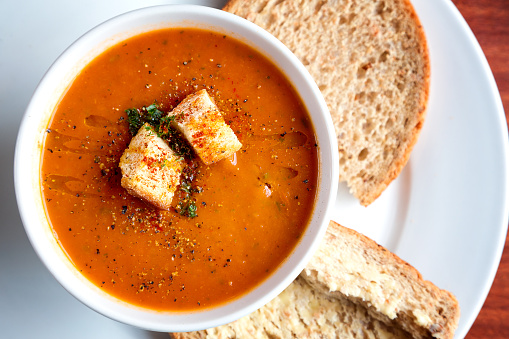 A bowl of fresh tomato soup in white ceramic bowl, garnished with herbs, croutons, seasoning and a drizzle of olive oil, and served with crusty wholemeal bread.
