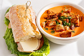 Bowl of cream of tomato soup with Turkey and Cheese sandwich
