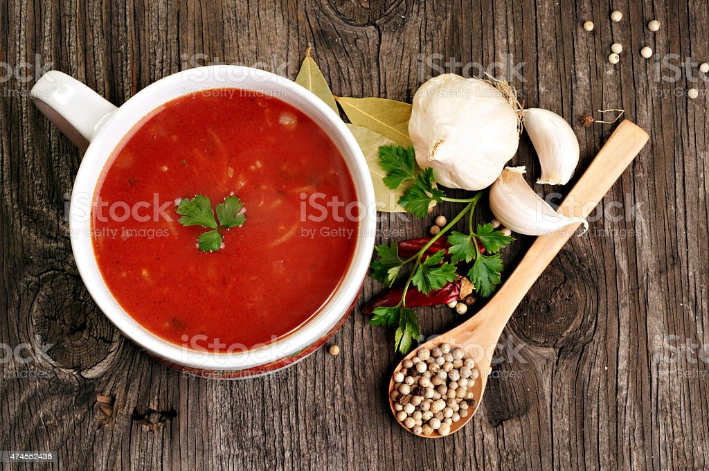 Tomato soup and spices on wooden table stock photo
