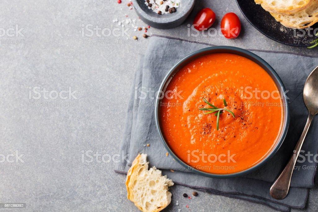 Tomato soup in a black bowl on grey stone background. Top view. Copy space. stock photo