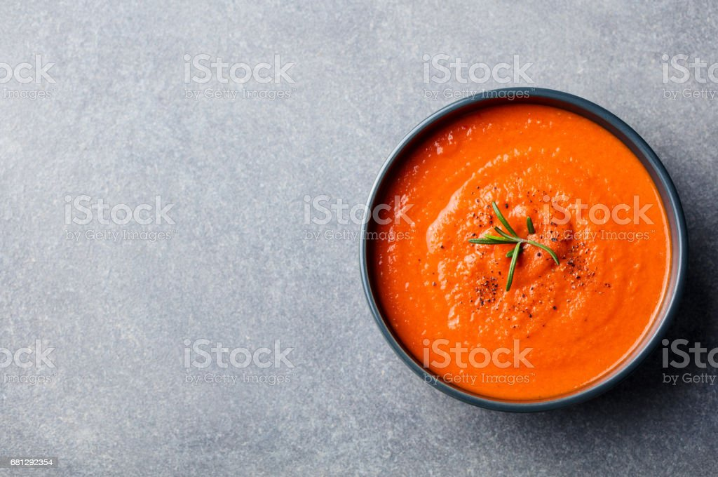 Tomato soup in a black bowl on grey stone background. Top view. Copy space stock photo