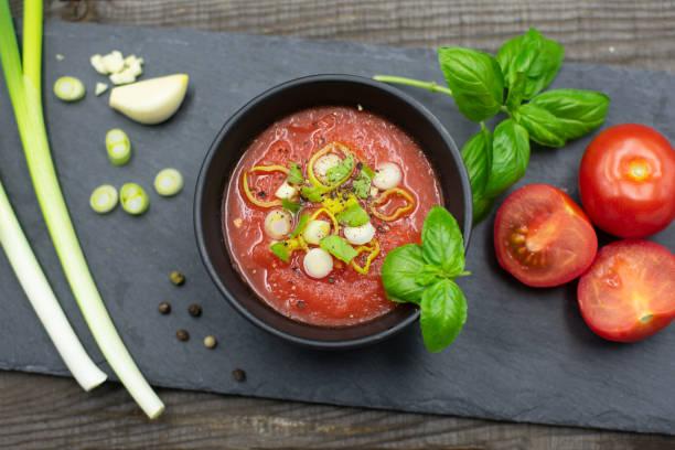 Tomatensuppe in einer kleinen Schüssel mit Frühlingszwiebeln, Pfeffer und Basilikum. Blick von oben – Foto