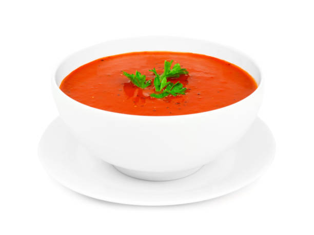 Tomato soup in a white bowl with saucer isolated on white stock photo