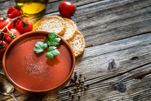 tomatensuppe auf rustikalem holztisch mit kopierraum - kalte tomatensuppe stock-fotos und bilder