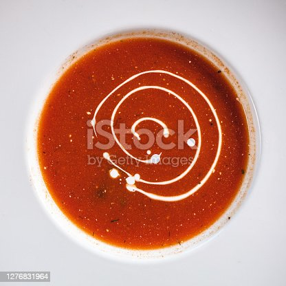Fresh tomato soup on wooden table background