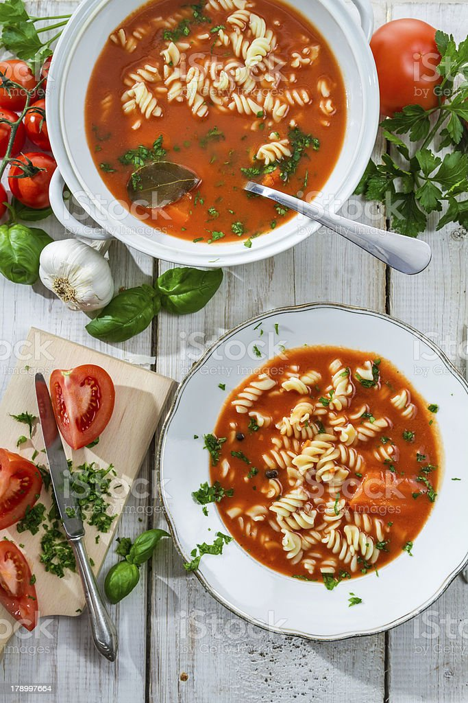 Tomato soup with noodle and ingredients on old wooden table royalty-free stock photo