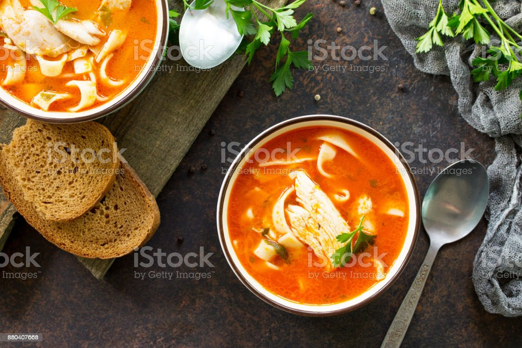 Tomato soup with pasta and chicken in a bowl on a dark stone background. The concept of healthy eating. Top view. stock photo