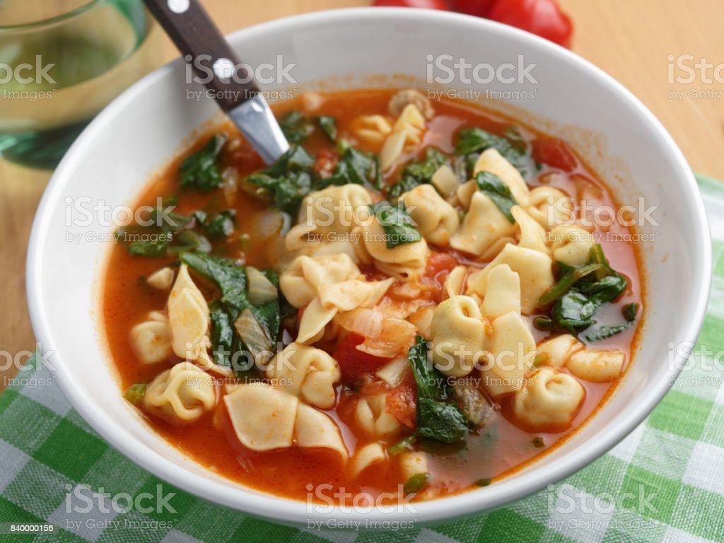 Tomato tortellini spinach soup stock photo