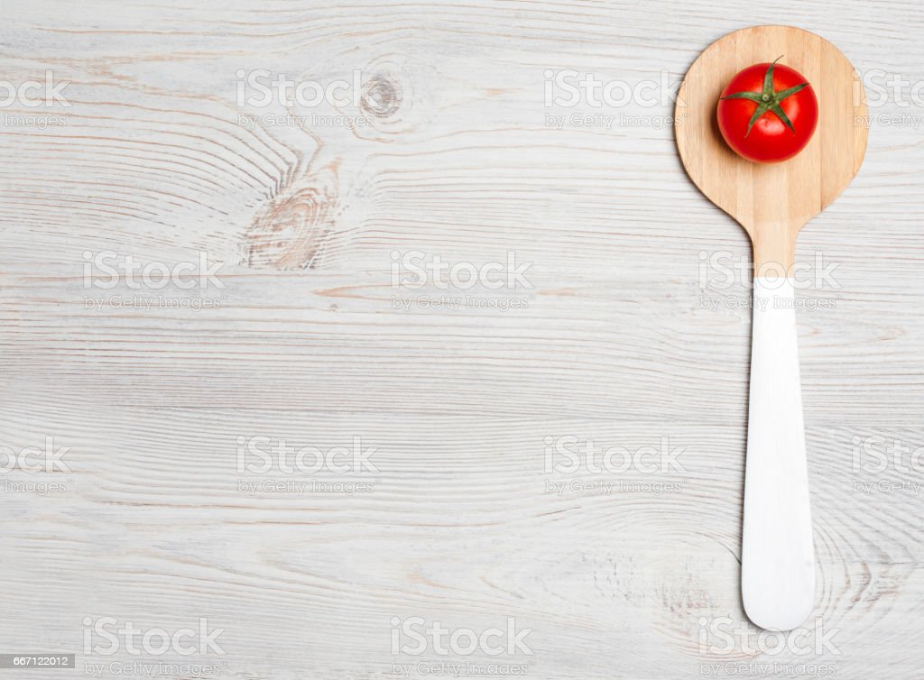 tomato with wooden cutlery on white wooden background stock photo