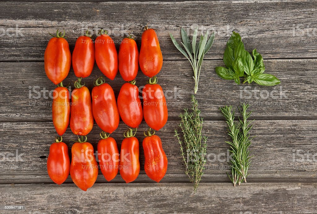 Tomatoes and herbs on the wooden board stock photo