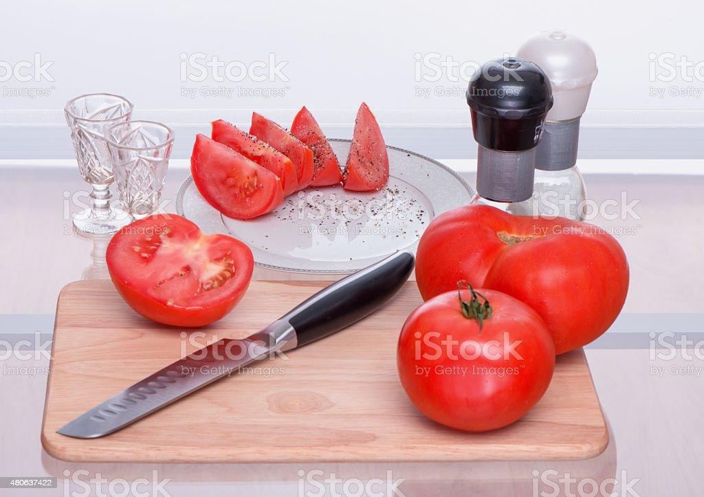Помидоры и нож на chopping доска стоковое фото