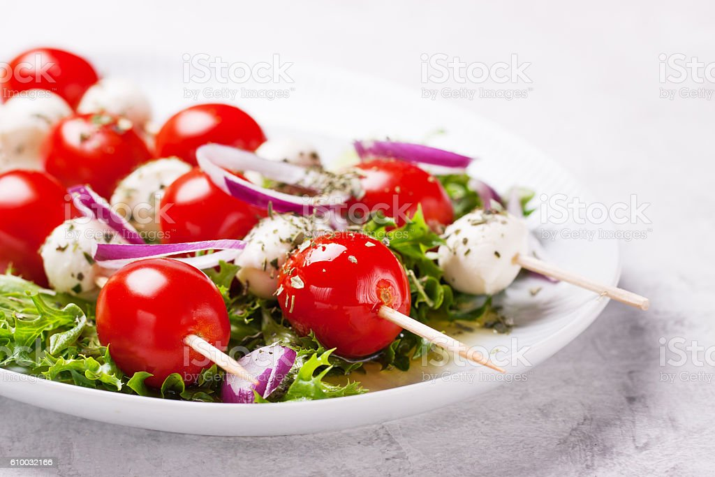 Tomatoes and mozzarella on sticks on salad leaves stock photo