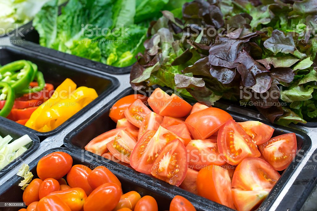 Tomatoes and other vegetables in salad trays stock photo